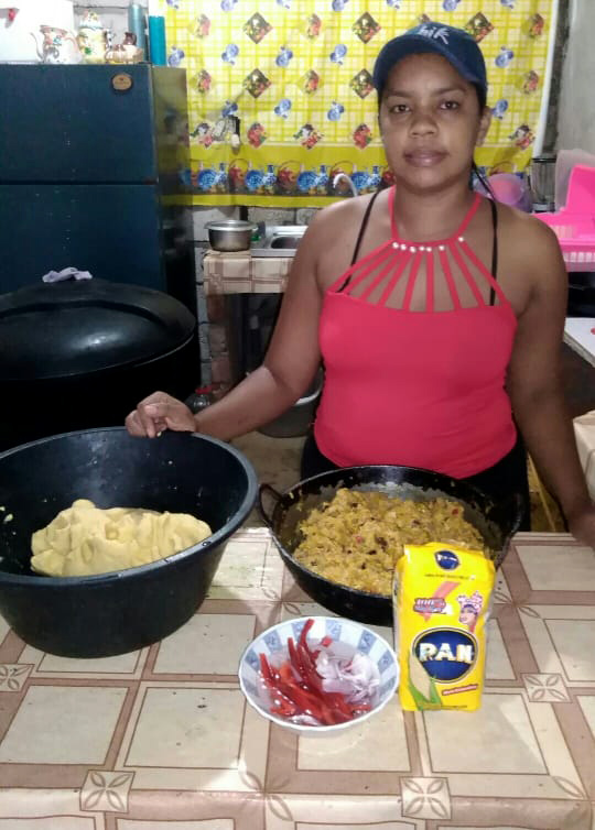 A woman prepares food in a kitchen.