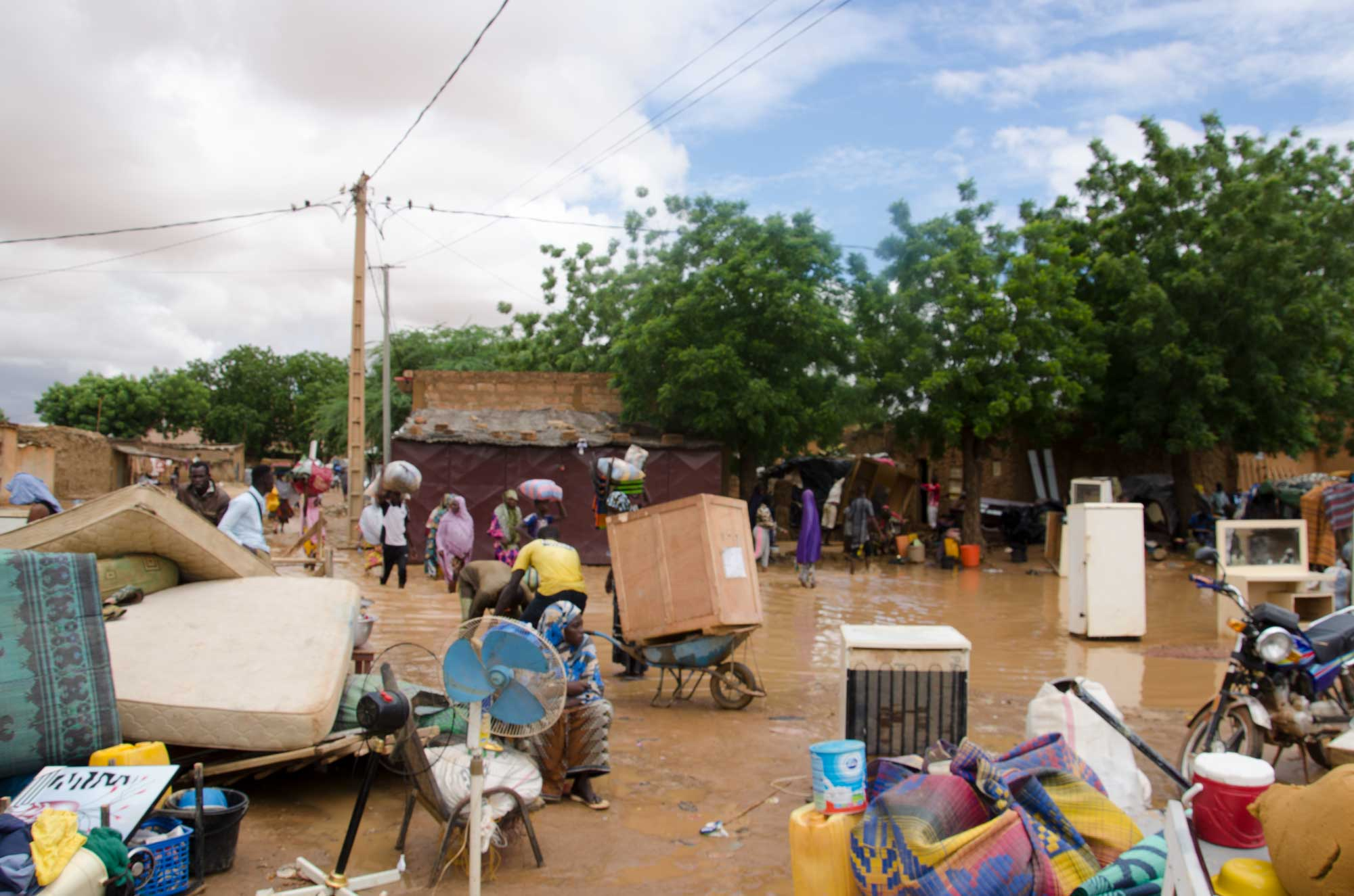 People with wheelbarrows and crass move around in floodwaters in a city street.