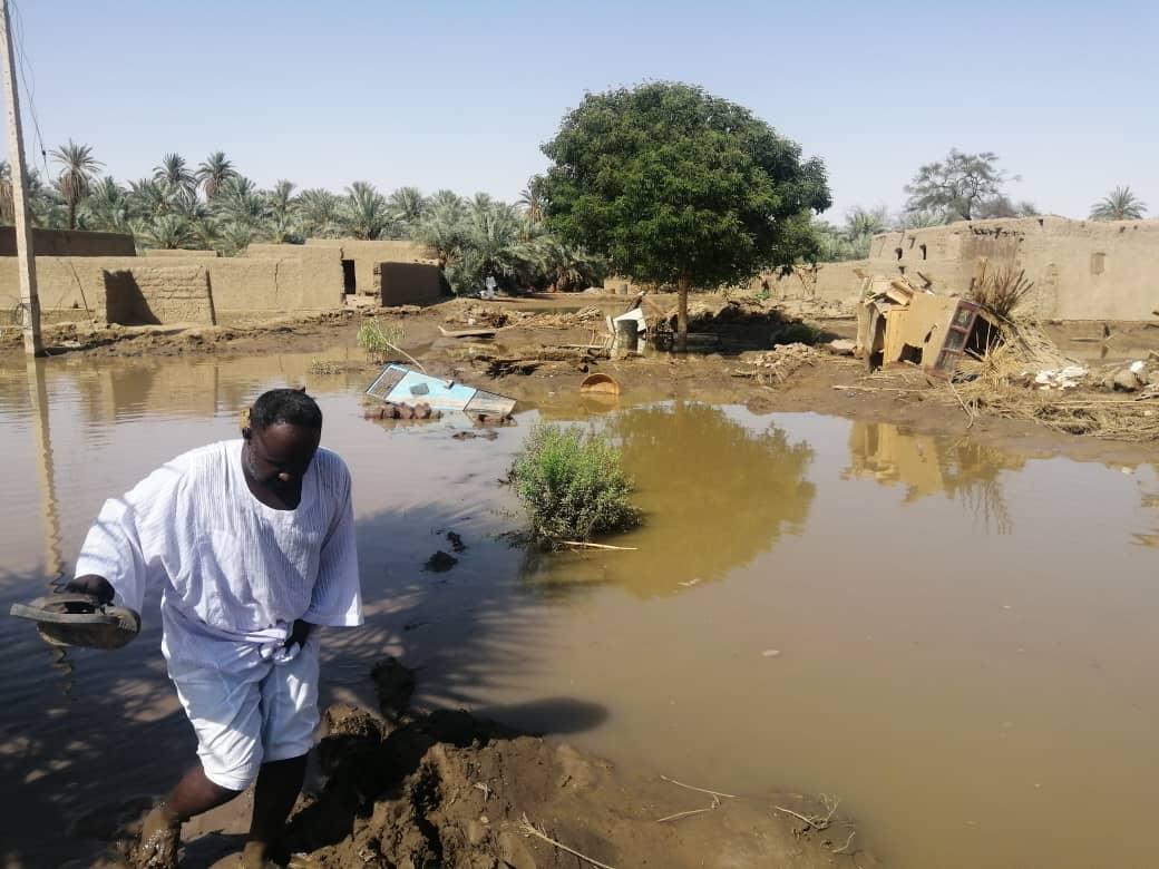 A man walks through flood waters in a muddy village.