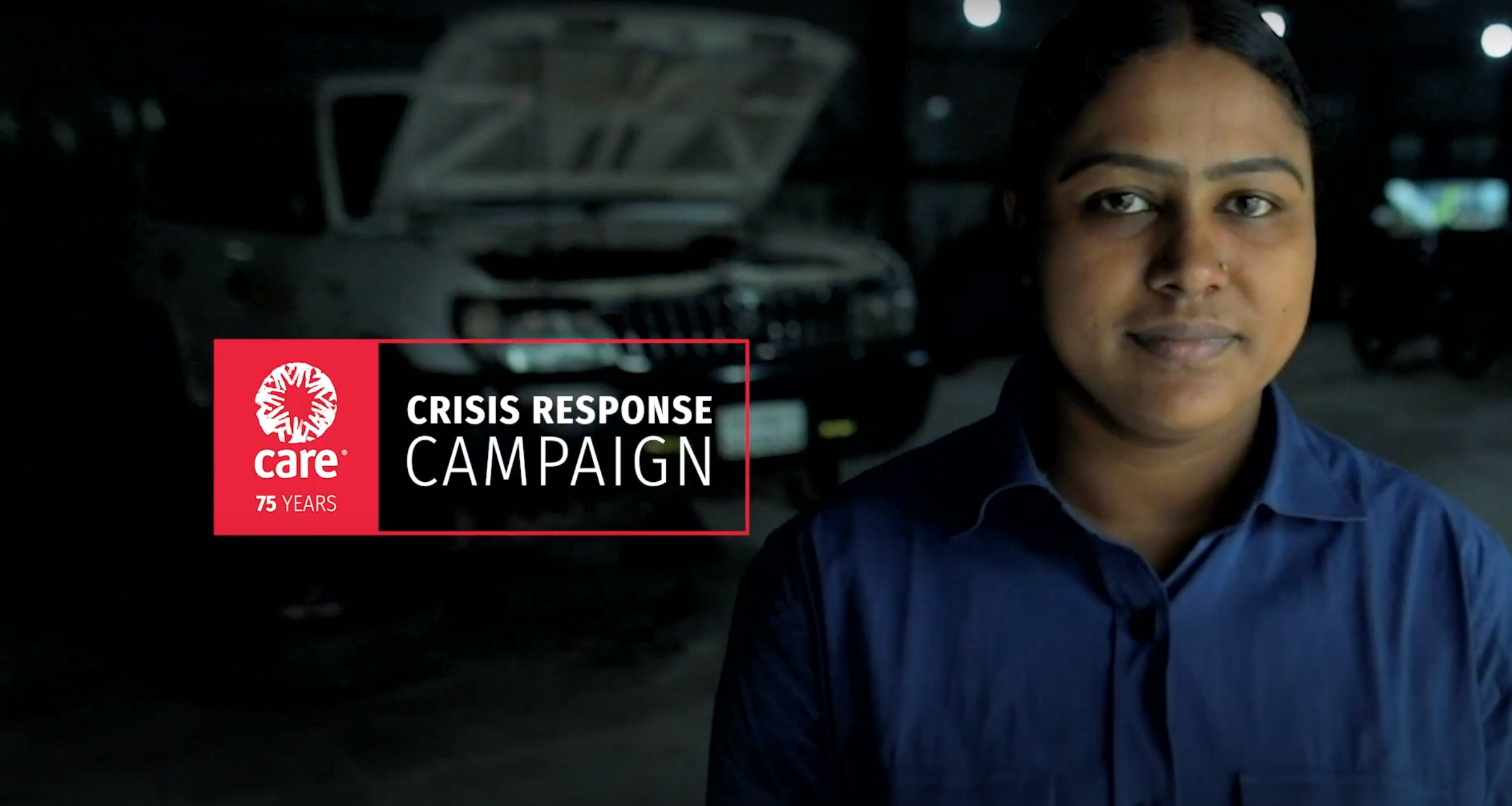 A woman wearing a dark blue mechanic's suit looks at the camera. Behind her is a car with the hood raised. Overlaid on top of the video is the CARE Crisis Response Campaign logo