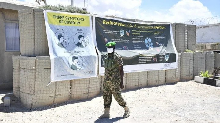 A soldier walks past a COVID-19 banner at Sector One headquarters in Mogadishu, Somalia. Photo by: AMISOM Photo / Steven Candia