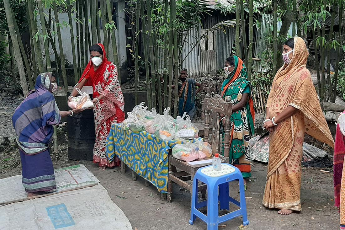Un groupe de femmes portant des vêtements aux couleurs vives et des masques blancs trie les fournitures.