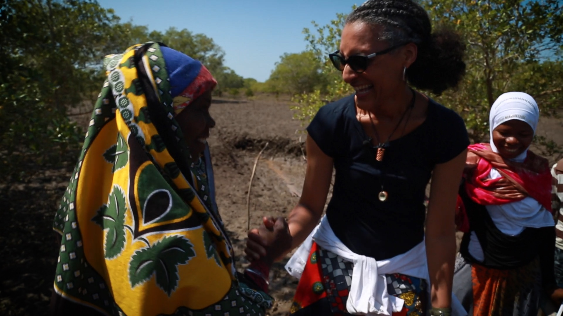 Two smiling women shake hands in a dirt field.