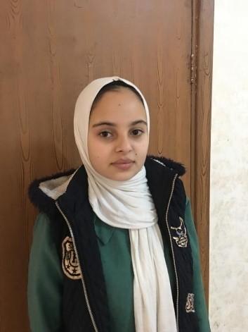 Uma adolescente está parada em frente a uma porta de madeira.