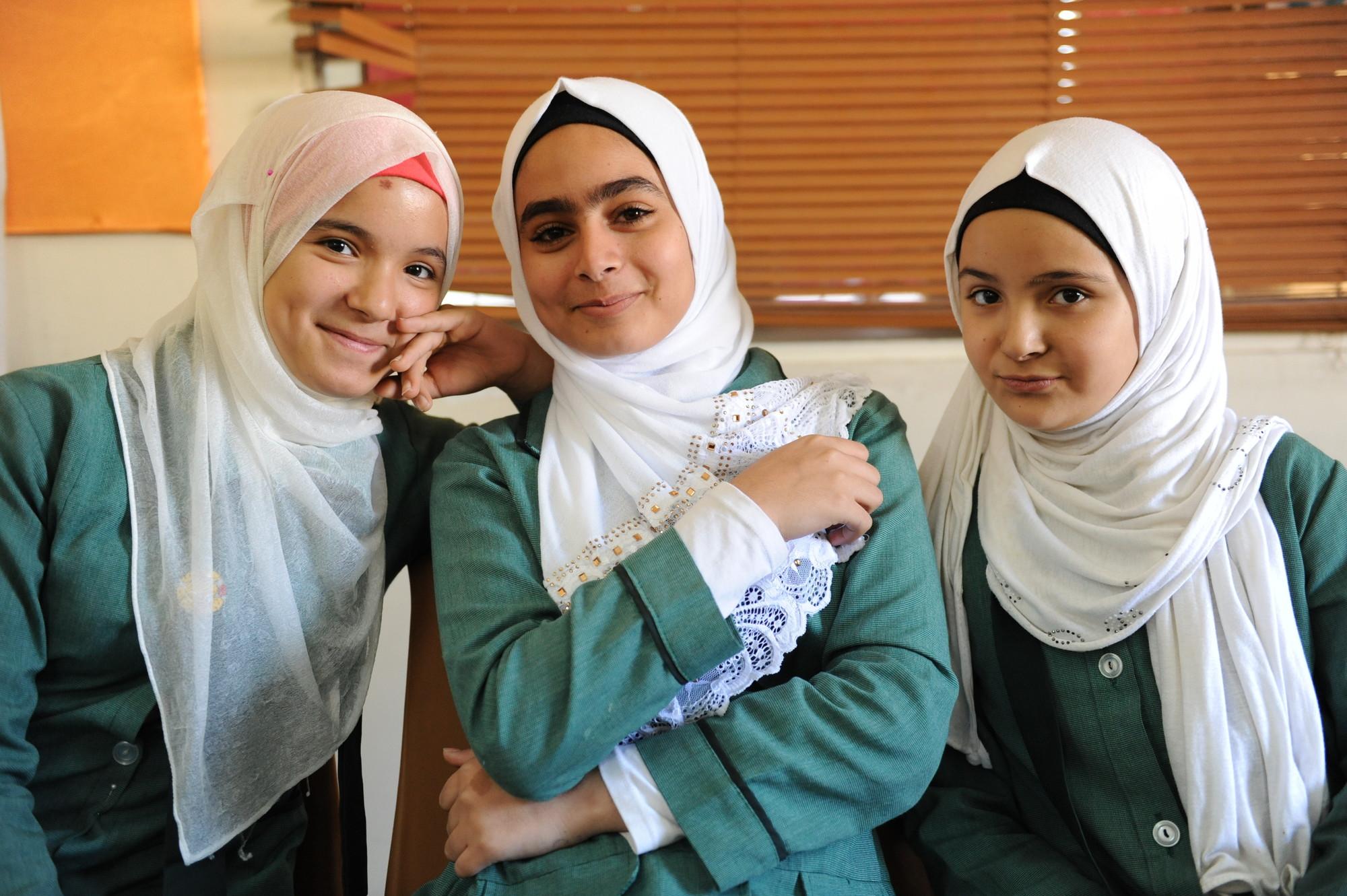 Three adolescent girls smile.
