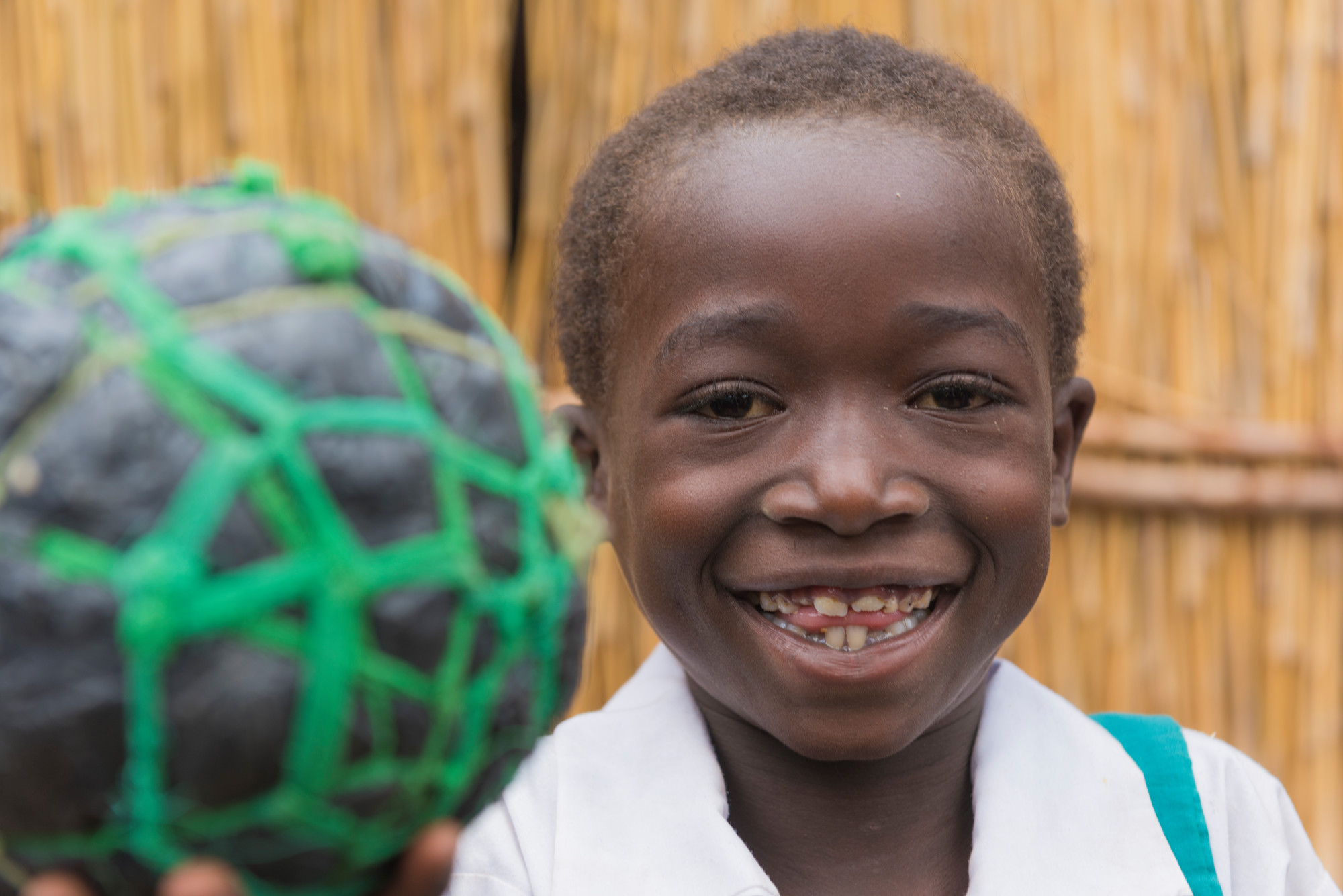 A young girl smiles wile holding an improvised soccer ball made of string and plastic bags.