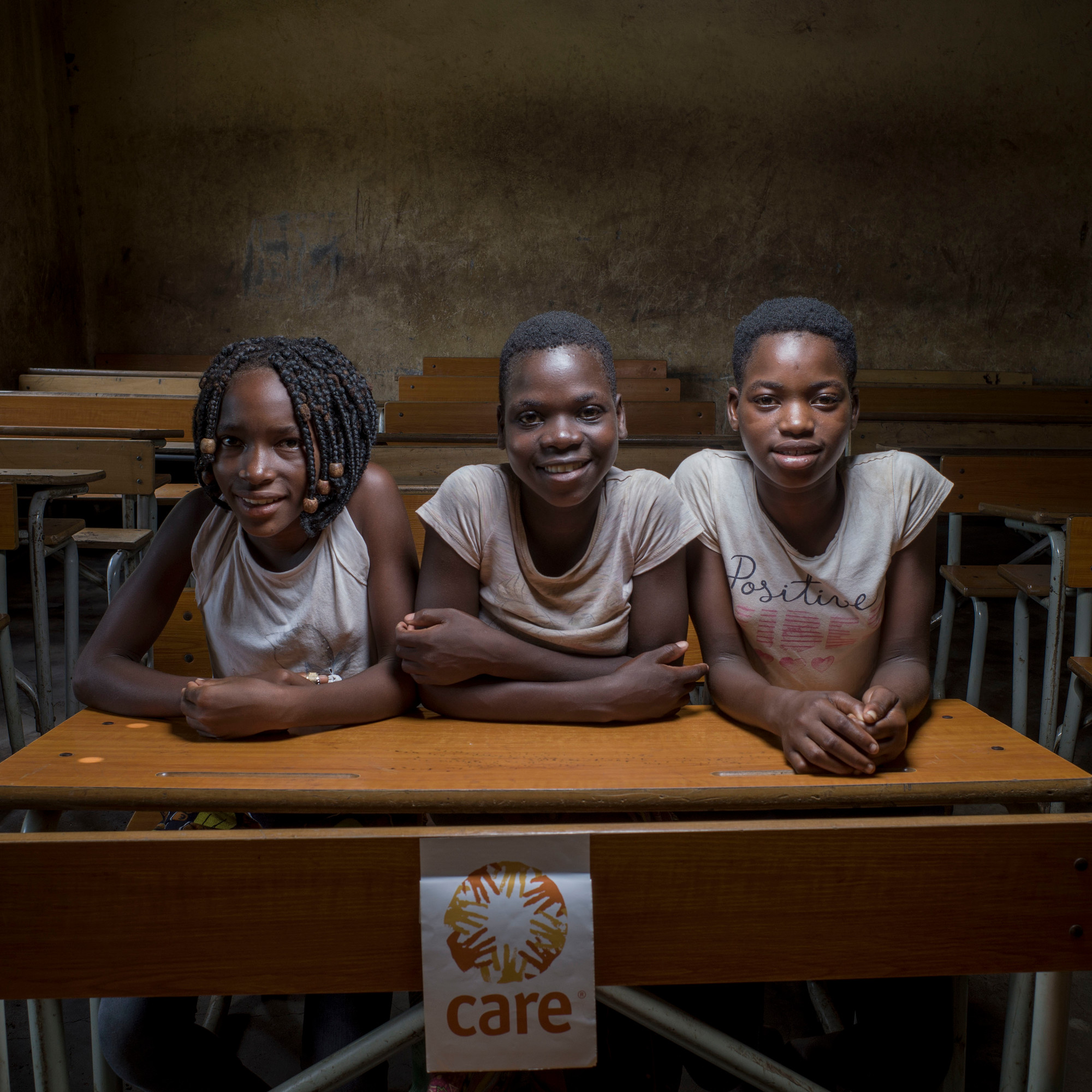 Three adolescent girls sit at a wooden desk in a classroom.