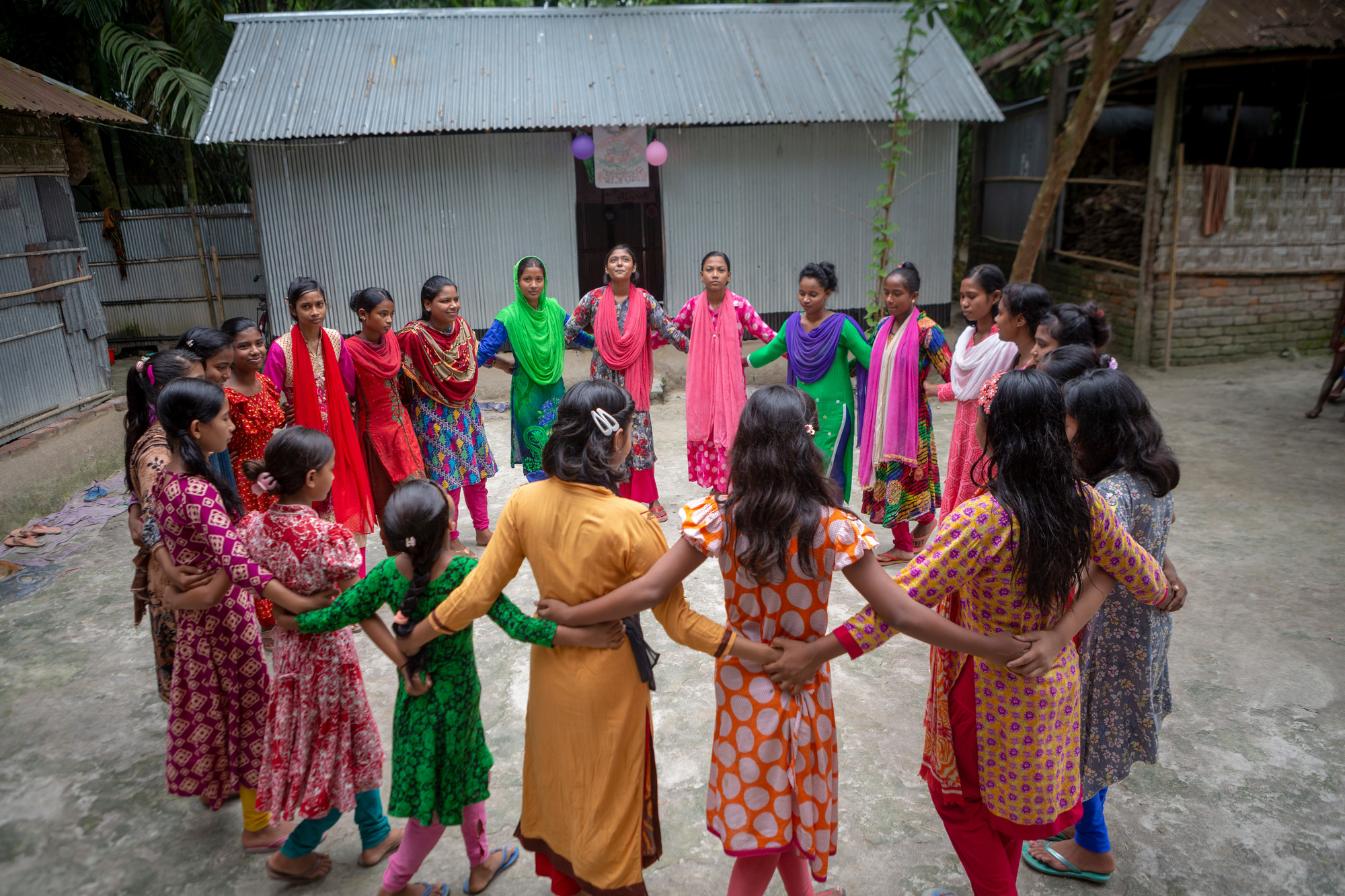 A group of adolescent girls stand in a circle outdoors in a village.