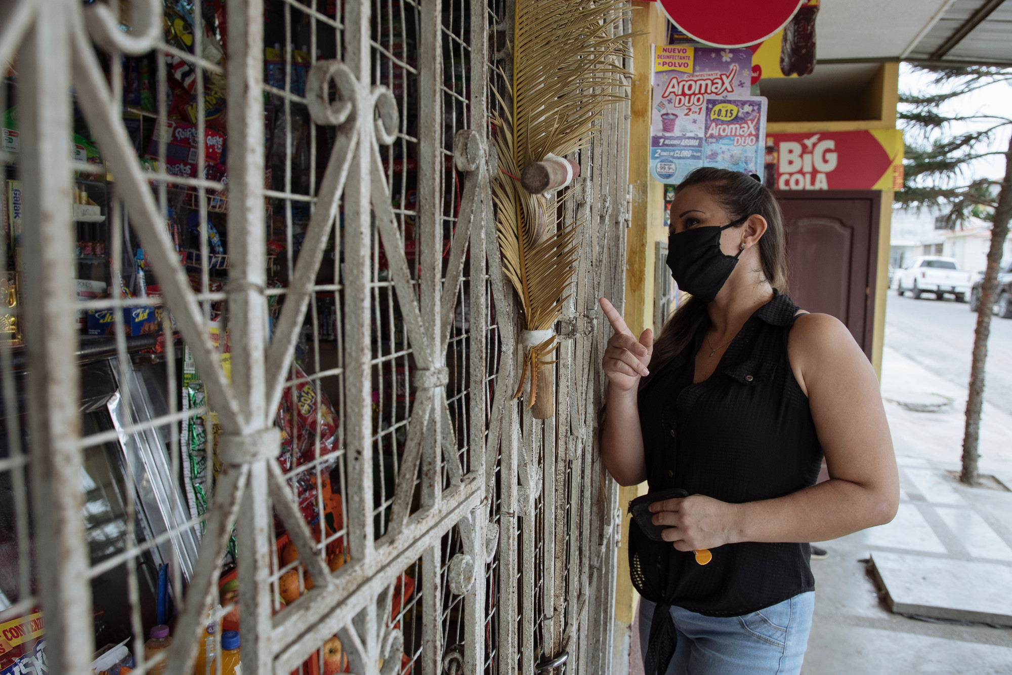 A woman in a face mask stands outside of a small store in a city.