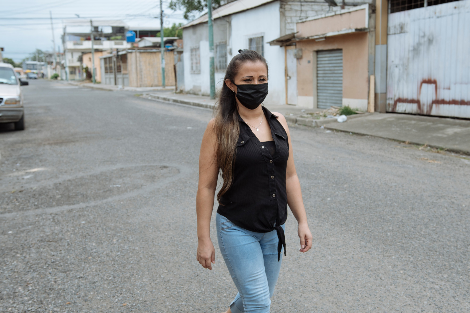 A woman in a face mask walks in an empty city street.