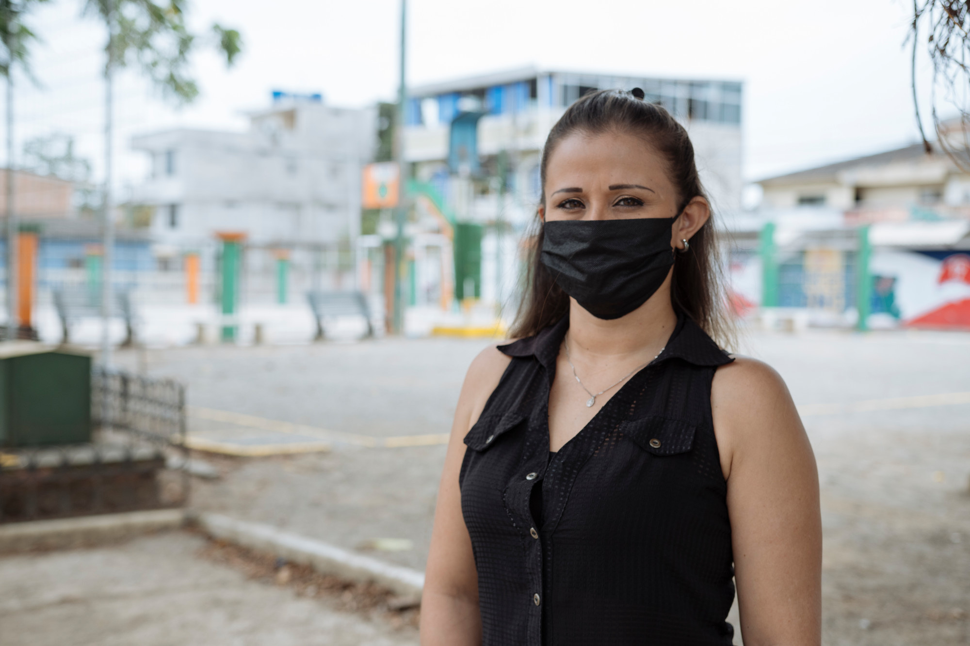 A woman in a face mask stands on a city street.