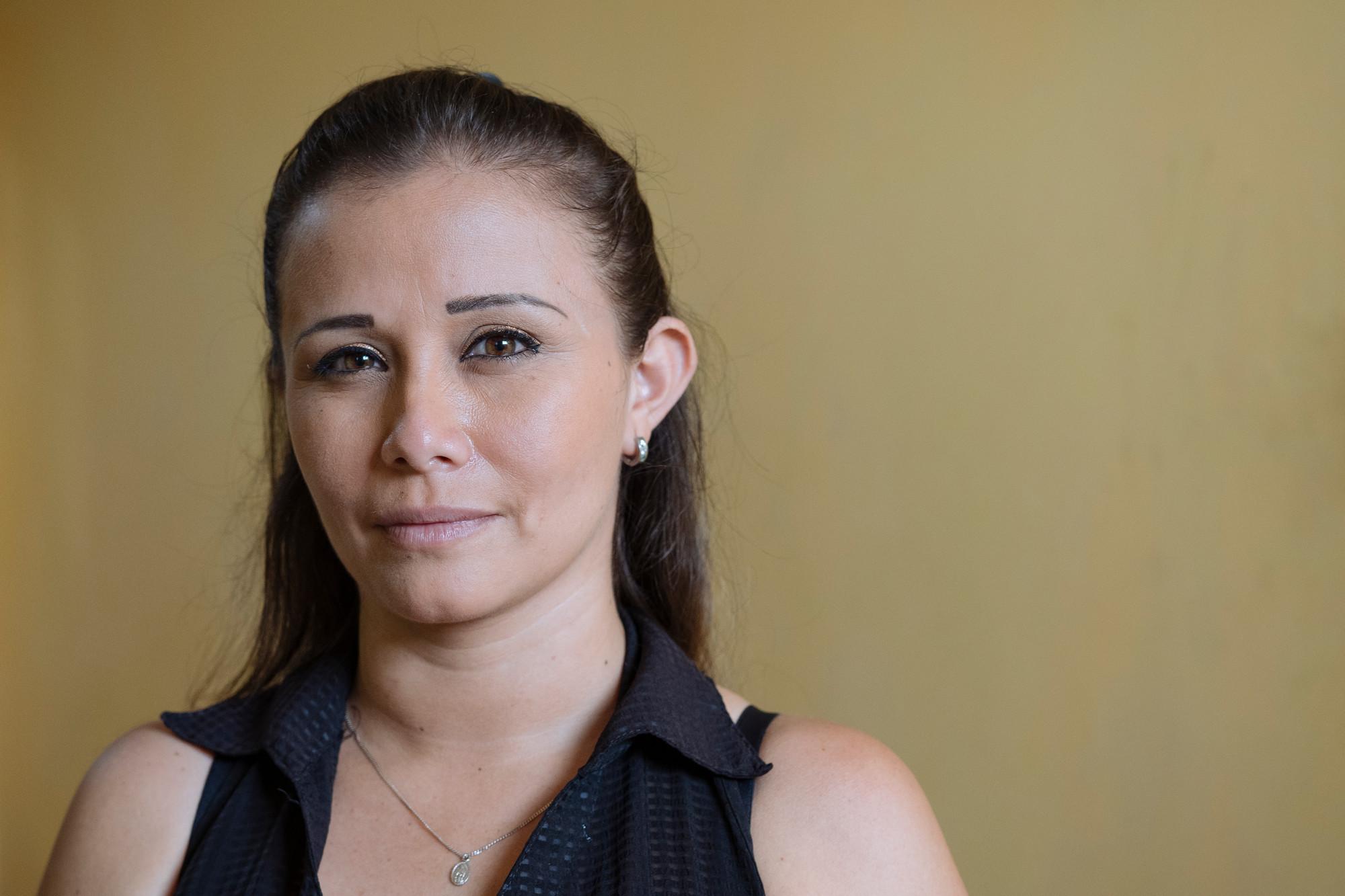 Uma mulher olha para a frente enquanto está dentro de seu apartamento.