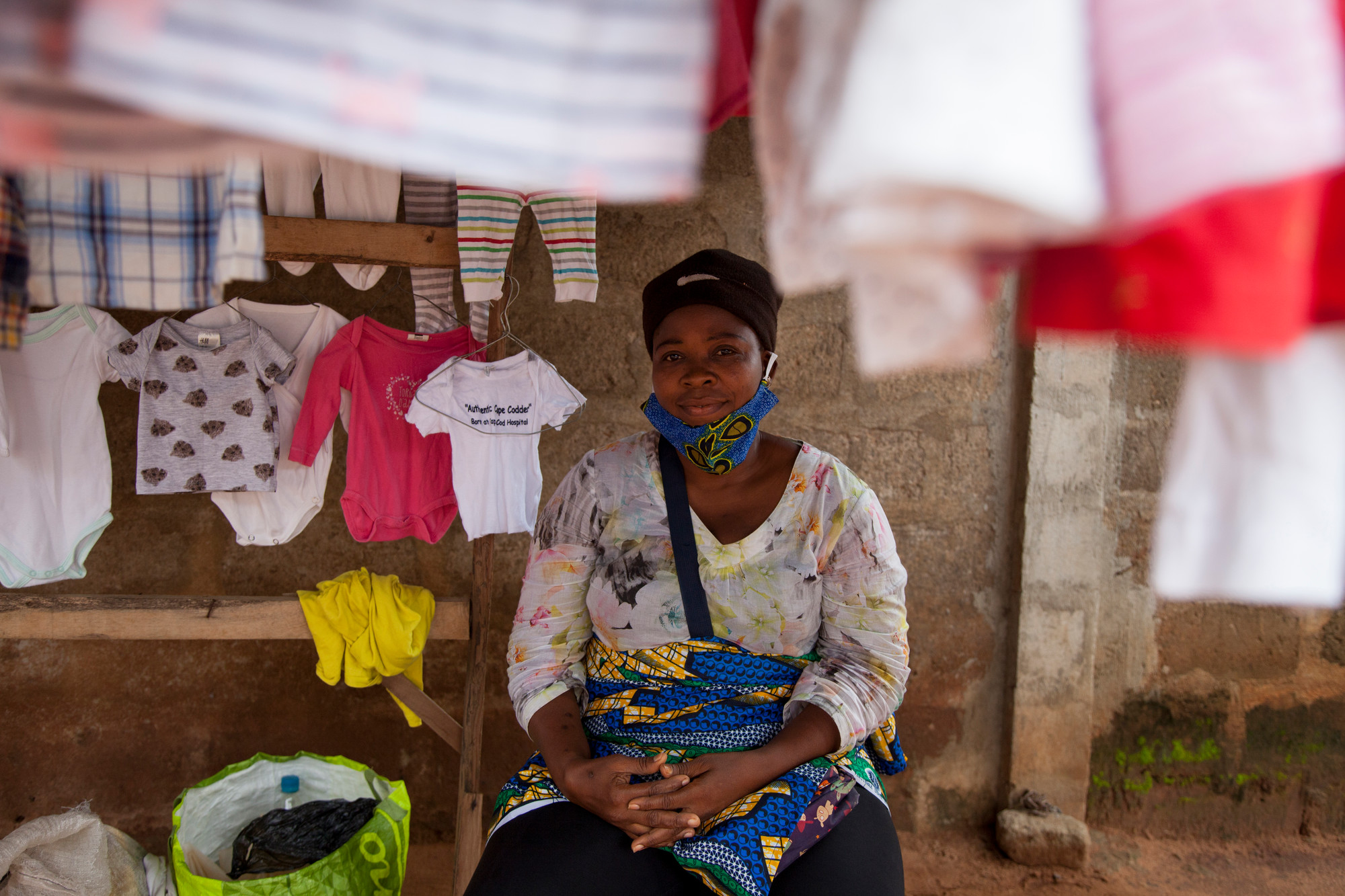 A woman sits in a stall selling clothes in an open-air market.
