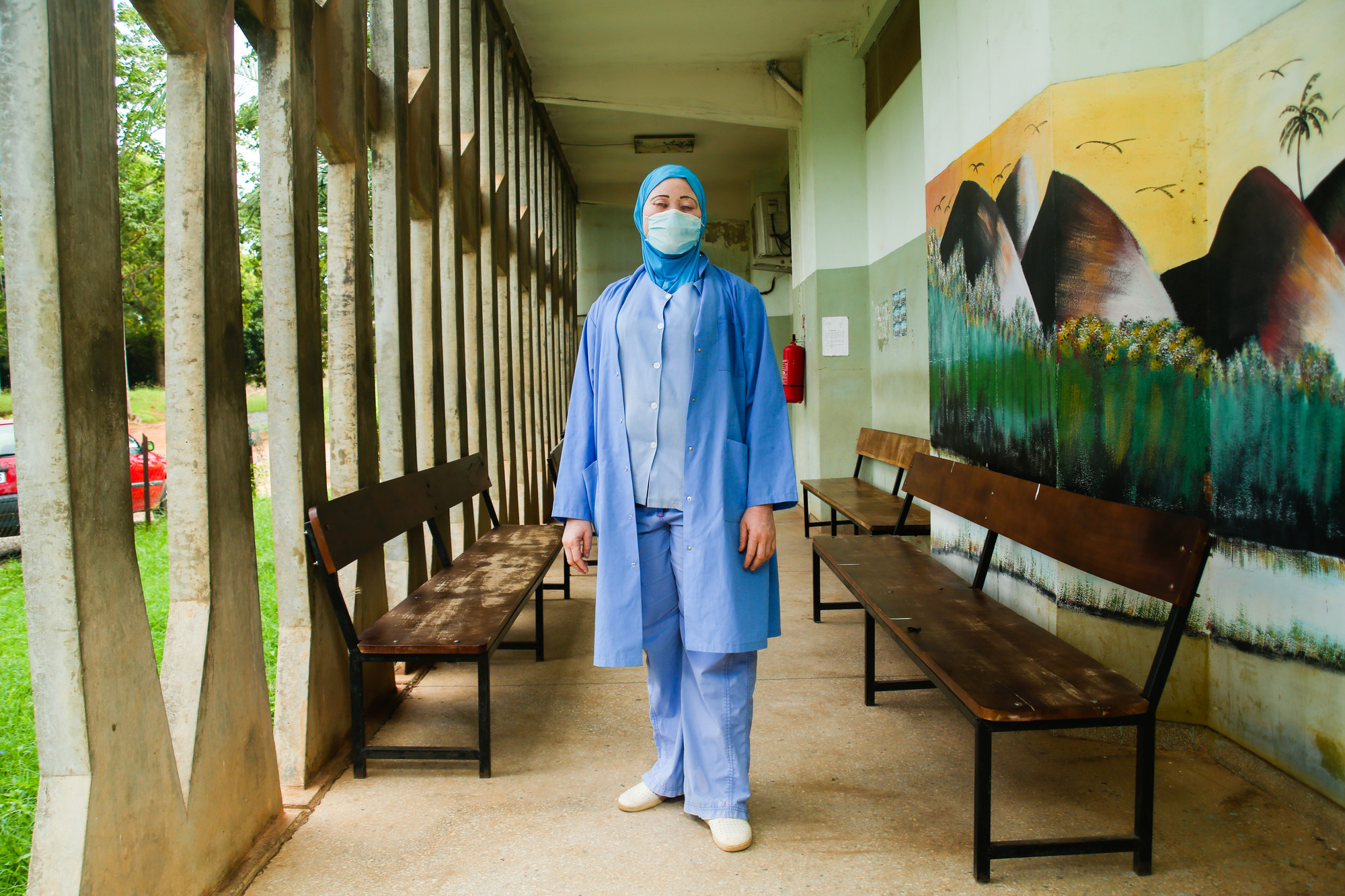 A woman in face mask and scrubs stands in a hallway.