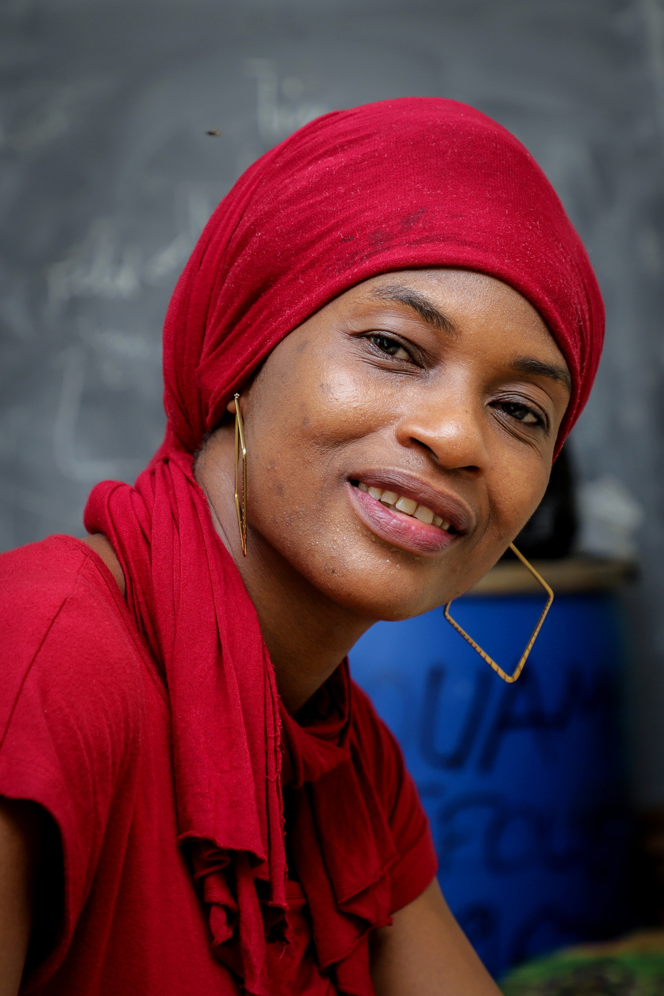 A woman in a red head wrap sits and smiles.