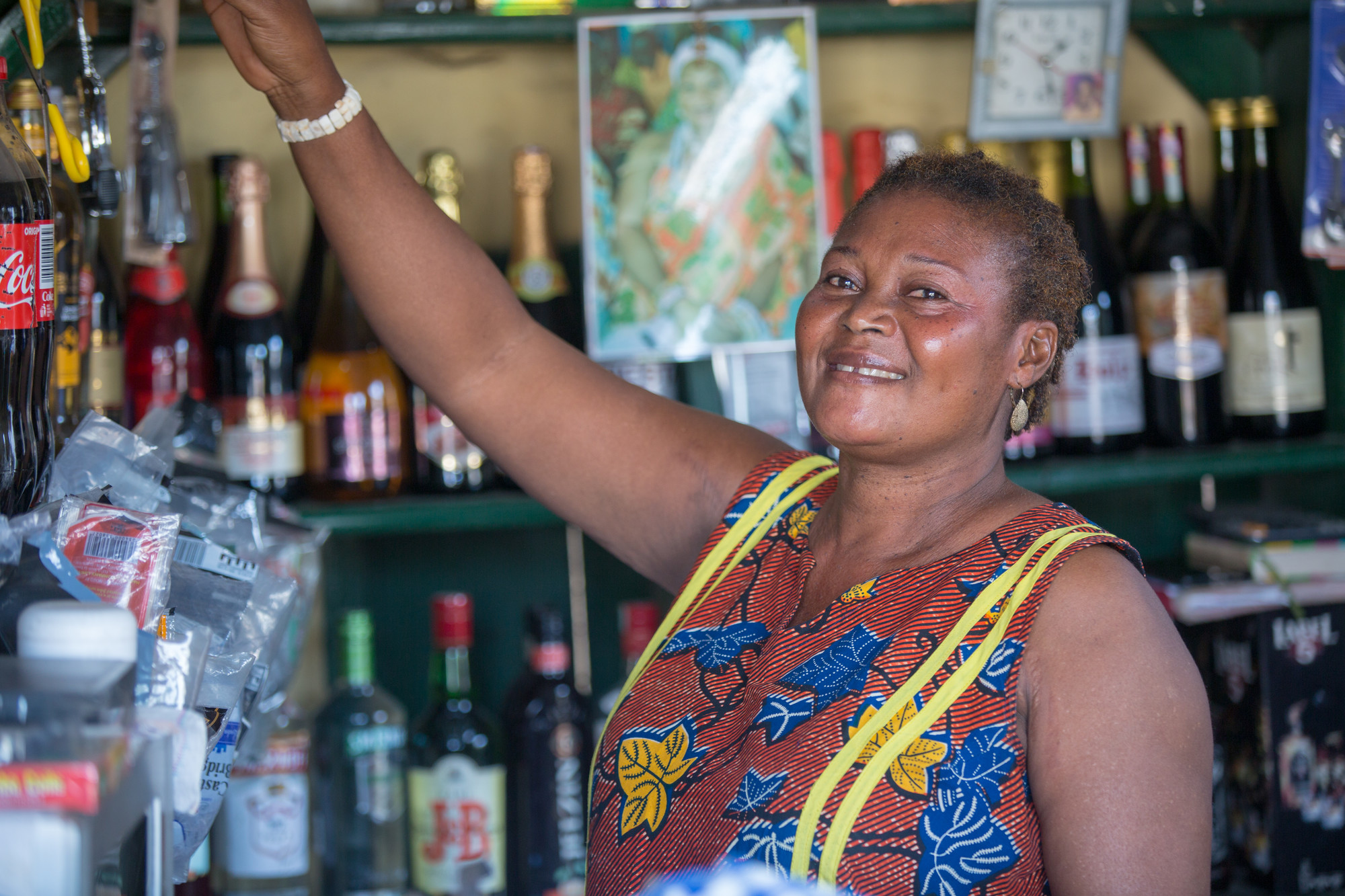 A woman smiles while reaching up to a shelf in a bar.