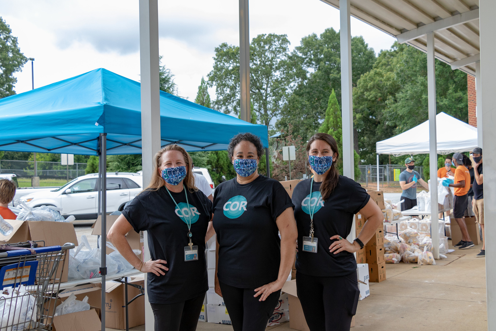 Three women in face masks stand behind a tent set up at a food distribution site.