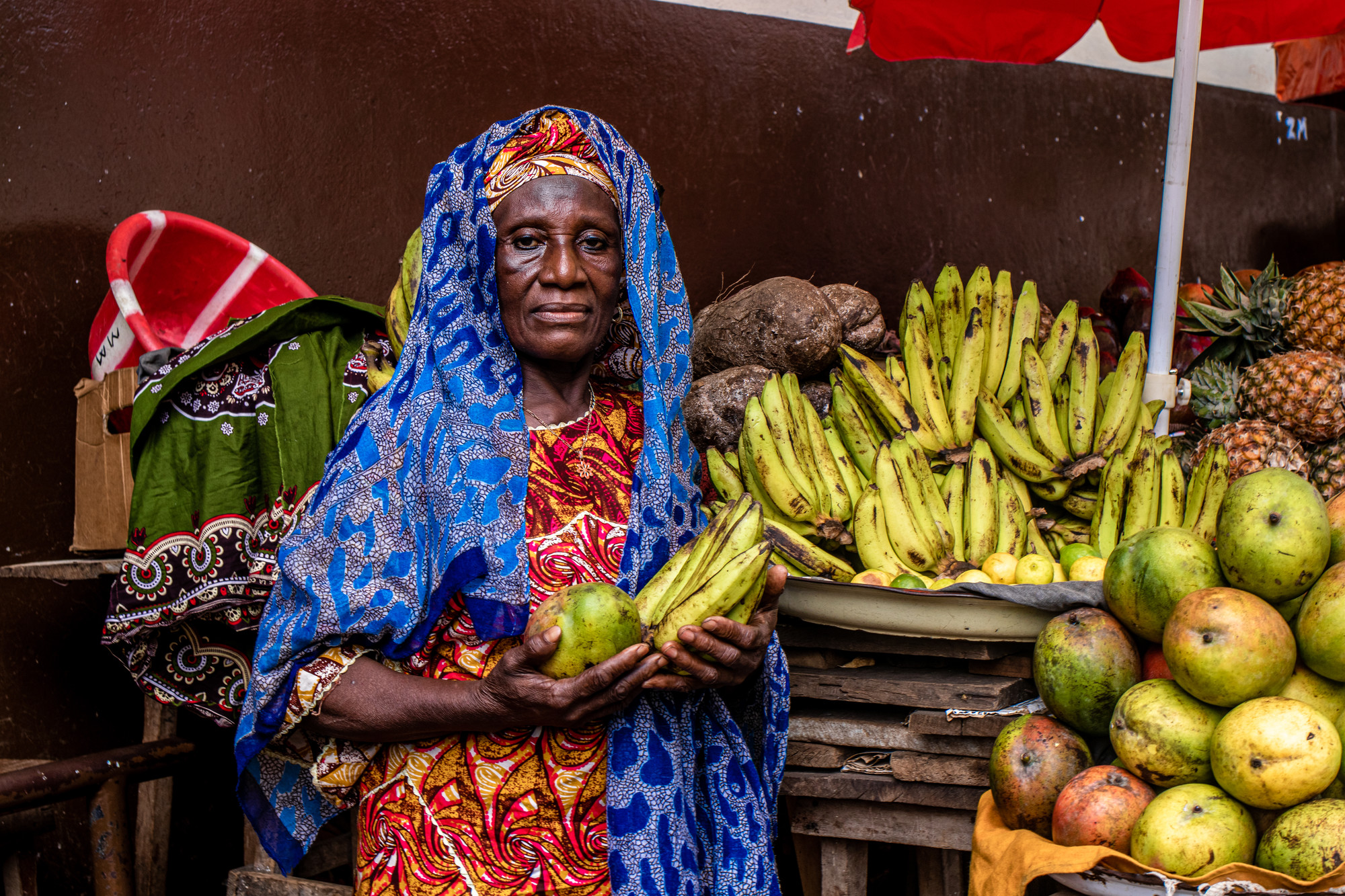 A woman at a fruit stand holds bananas and other fruits.