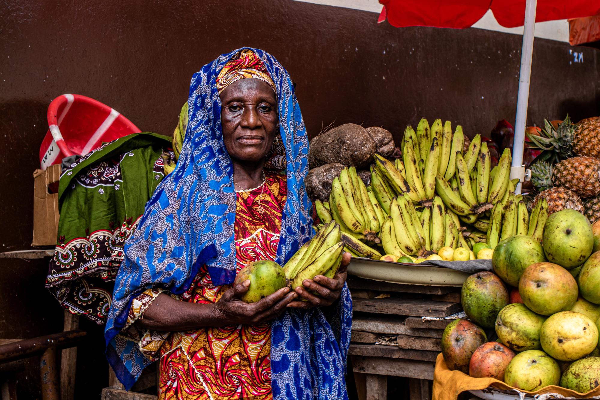 Una mujer en un puesto de frutas sostiene plátanos y otras frutas.
