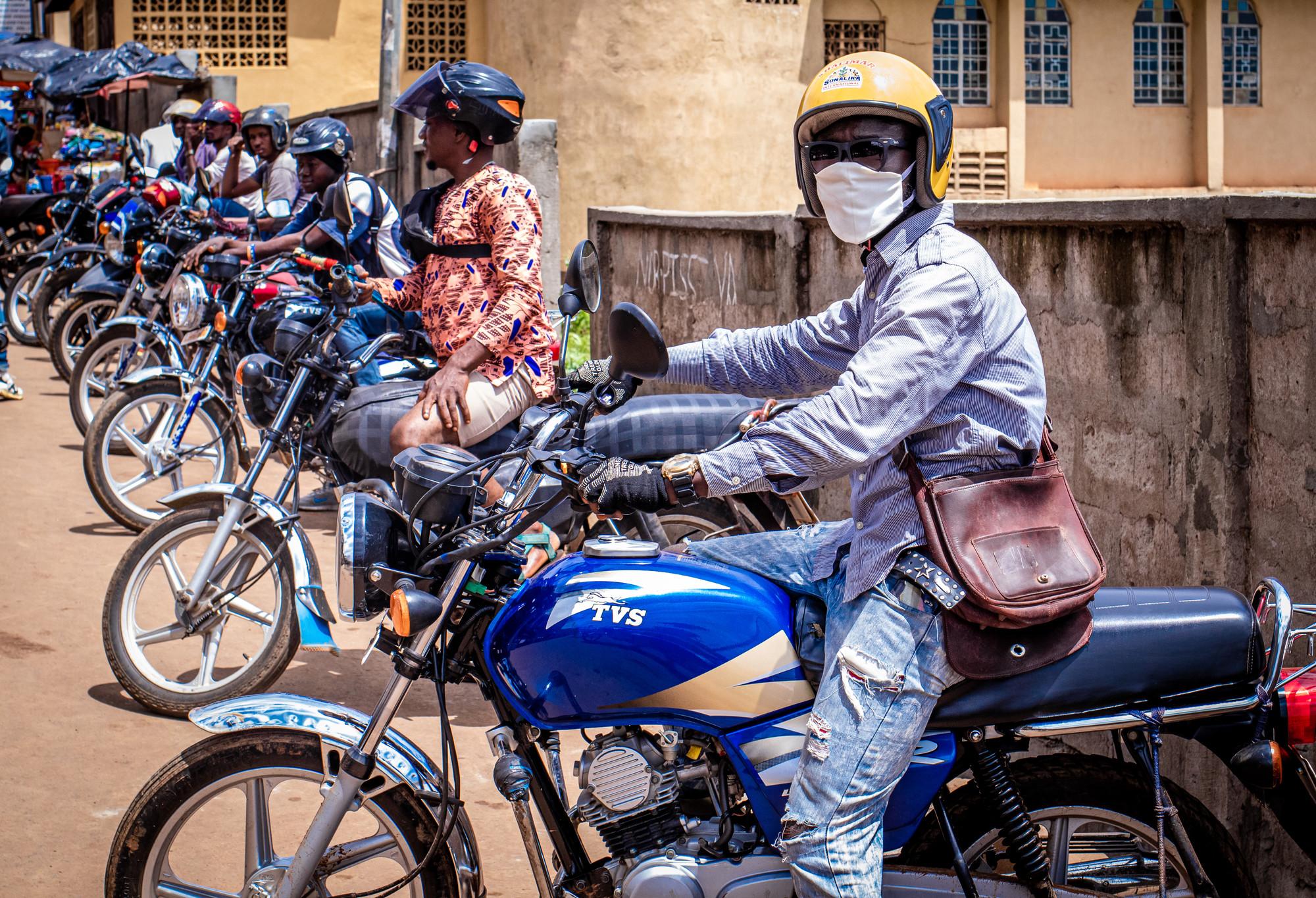 La gente se sienta en motocicletas estacionadas.