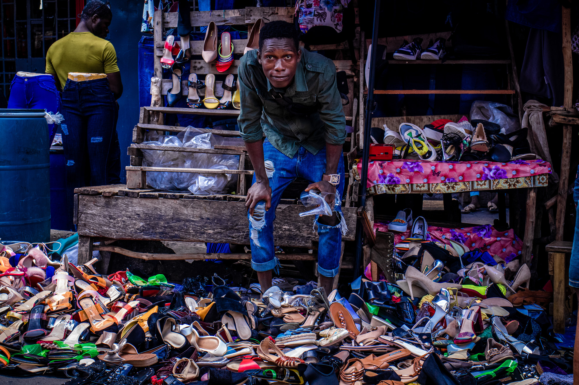 A man stands in front of bundles of shoes in an open-air stall.