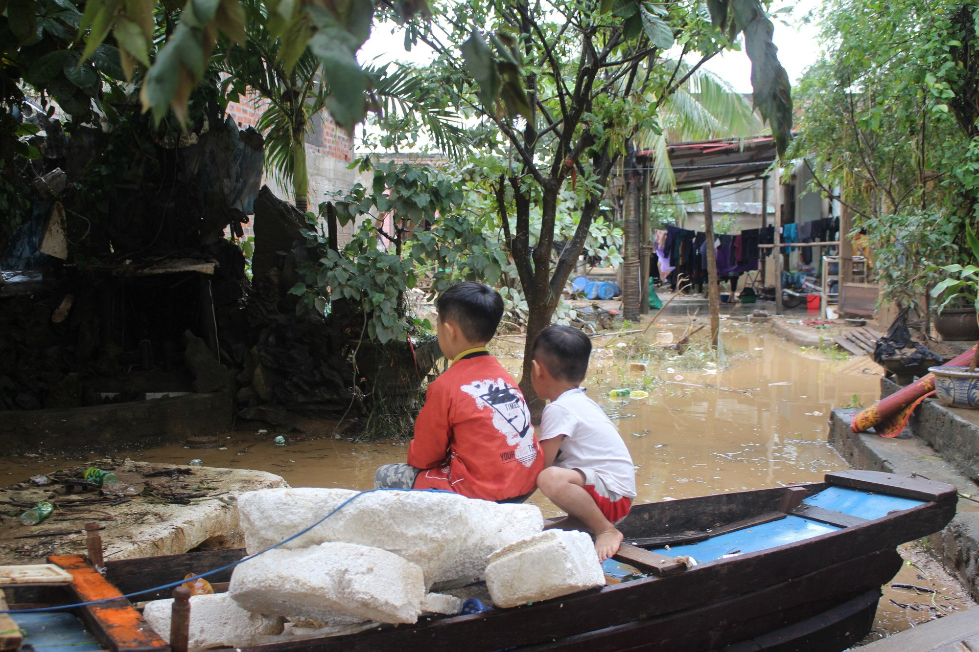 two children sit on a small boat in a flooded village.