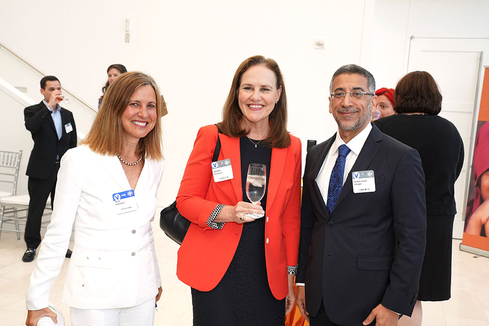 Michele Flournoy, former U.S. Undersecretary of Defense for Policy, wears a red blazer. She is posing for the camera with a woman wearing all-white and a man wearing a suit.
