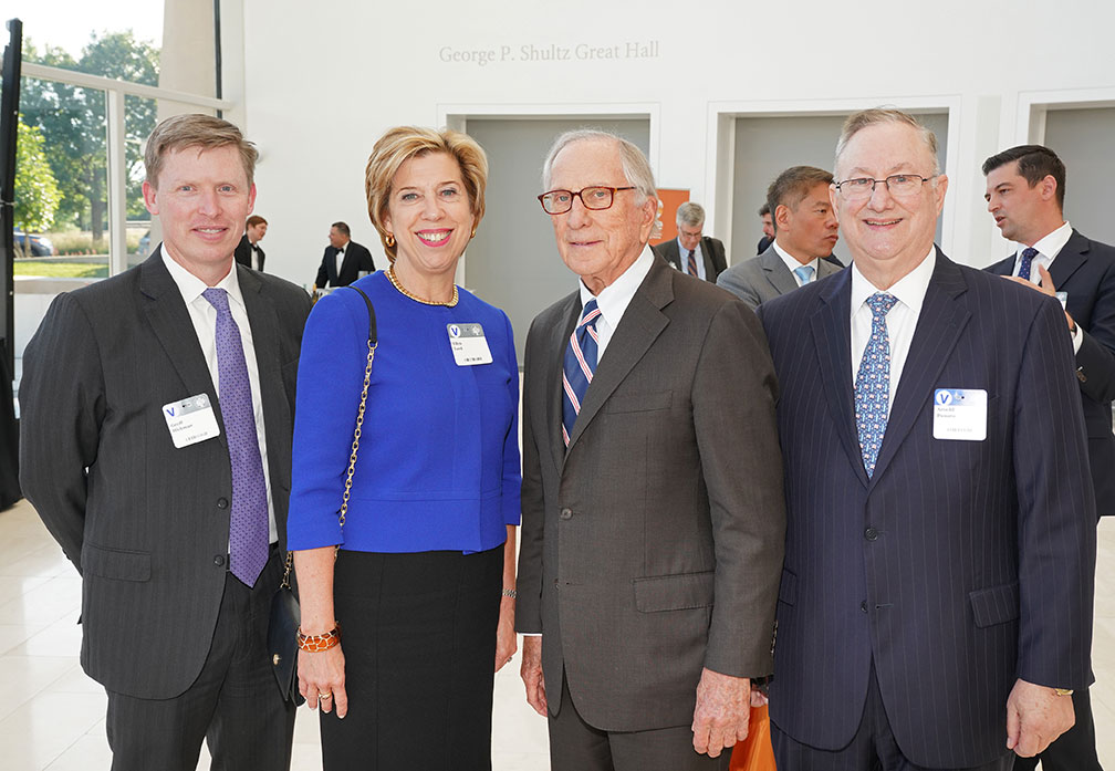 Four attendees - three men and one woman - pose for the camera at the Global Leaders Network Awards Reception.
