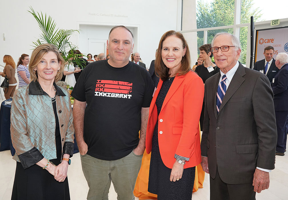 Michèle Flournoy, former U.S. Undersecretary of Defense for Policy, and chef José Andrés stand with two attendees at the Global Leaders Network Awards Reception. José Andrés wears a t-shirt that says,