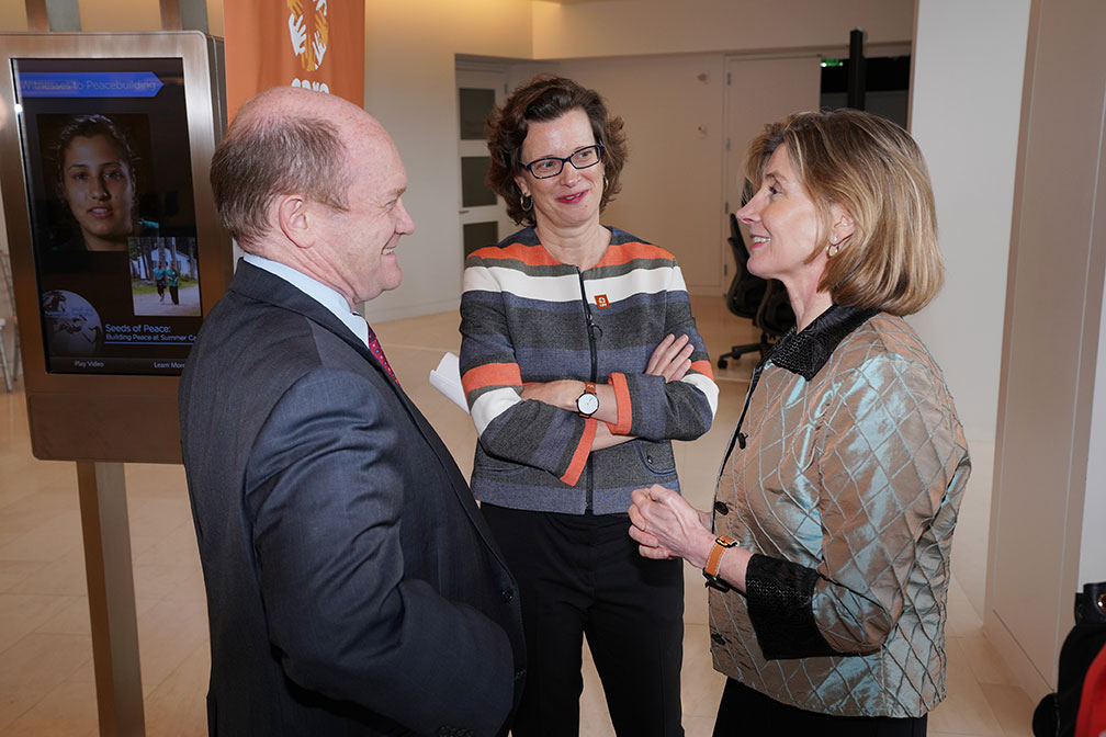 A man and two women talking.
