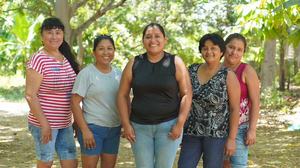 A group of Peruvian women stand together and smile outside under a large tree.