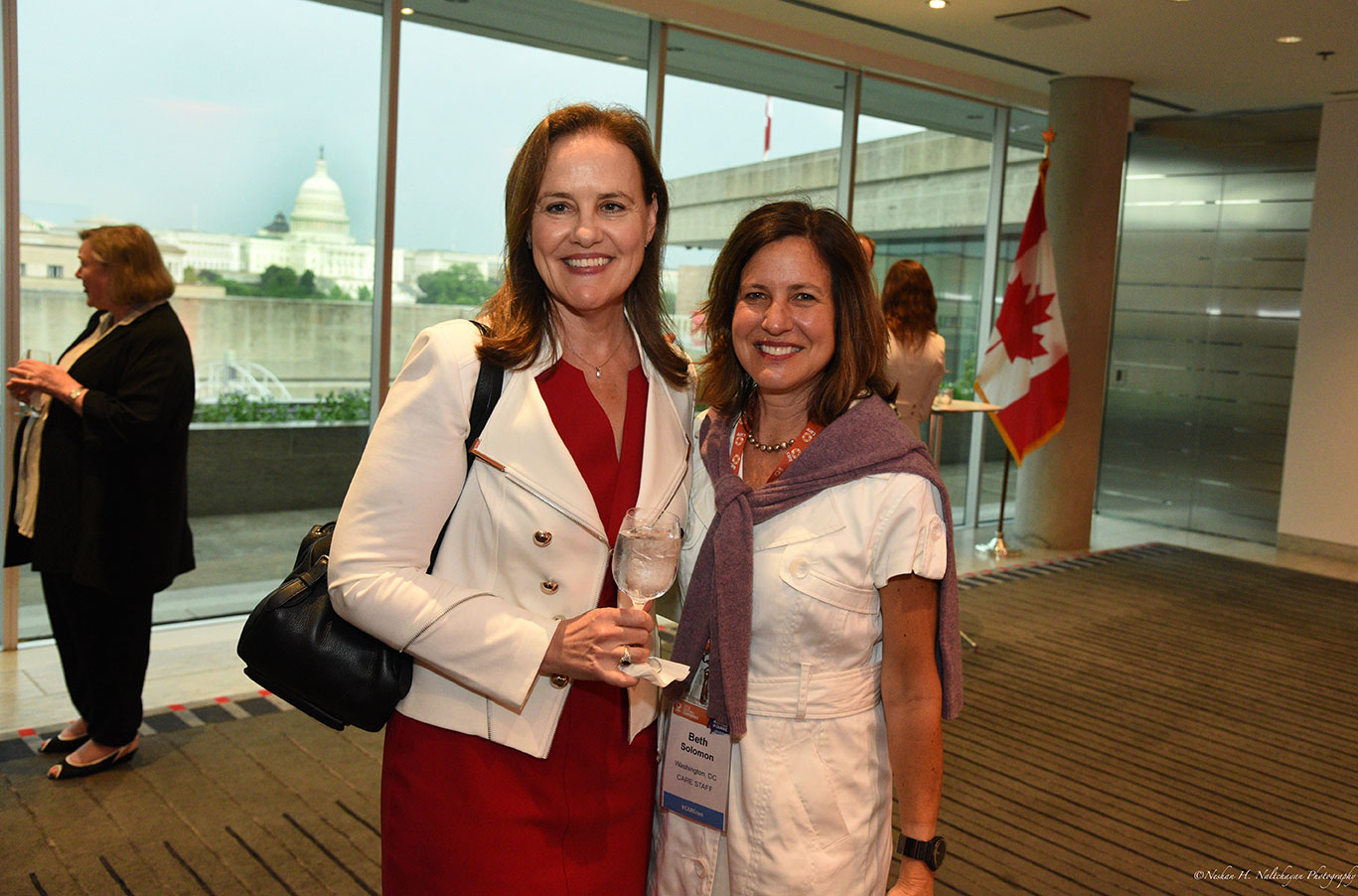 Michéle Flournoy enjoys a glass of water while standing next to Beth Solomon.
