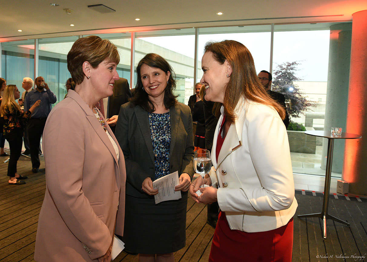 Michéle Flournoy, Minister Marie-Claude Bibeau, and another woman smile widely and talk with each other..