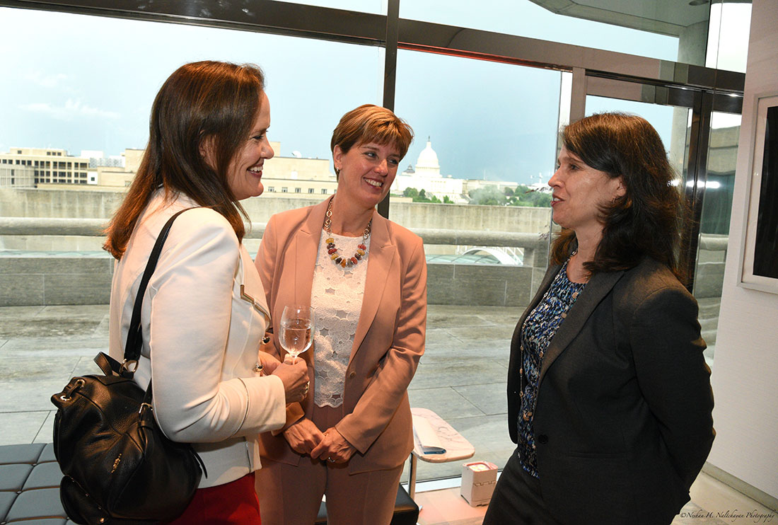 Michéle Flournoy, Minister Marie-Claude Bibeau, and another woman talk with each other..