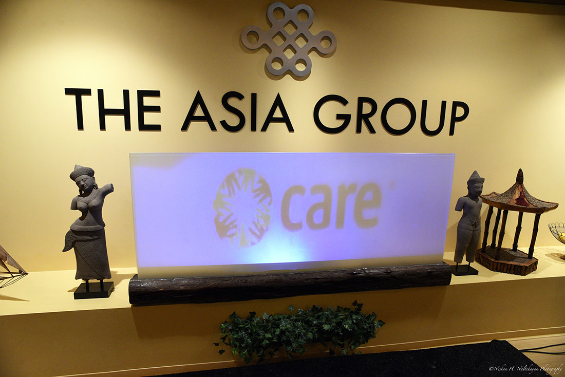 A wall lined with statues shows The Asia Group logo.