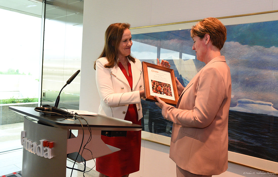 Former Under Secretary of Defense Michéle Flournoy, wearing a red dress and white jacket, hands the CARE Global Leaders Network Humanitarian Award to Minister Marie-Claude Bibeau, wearing a blush pink suit.