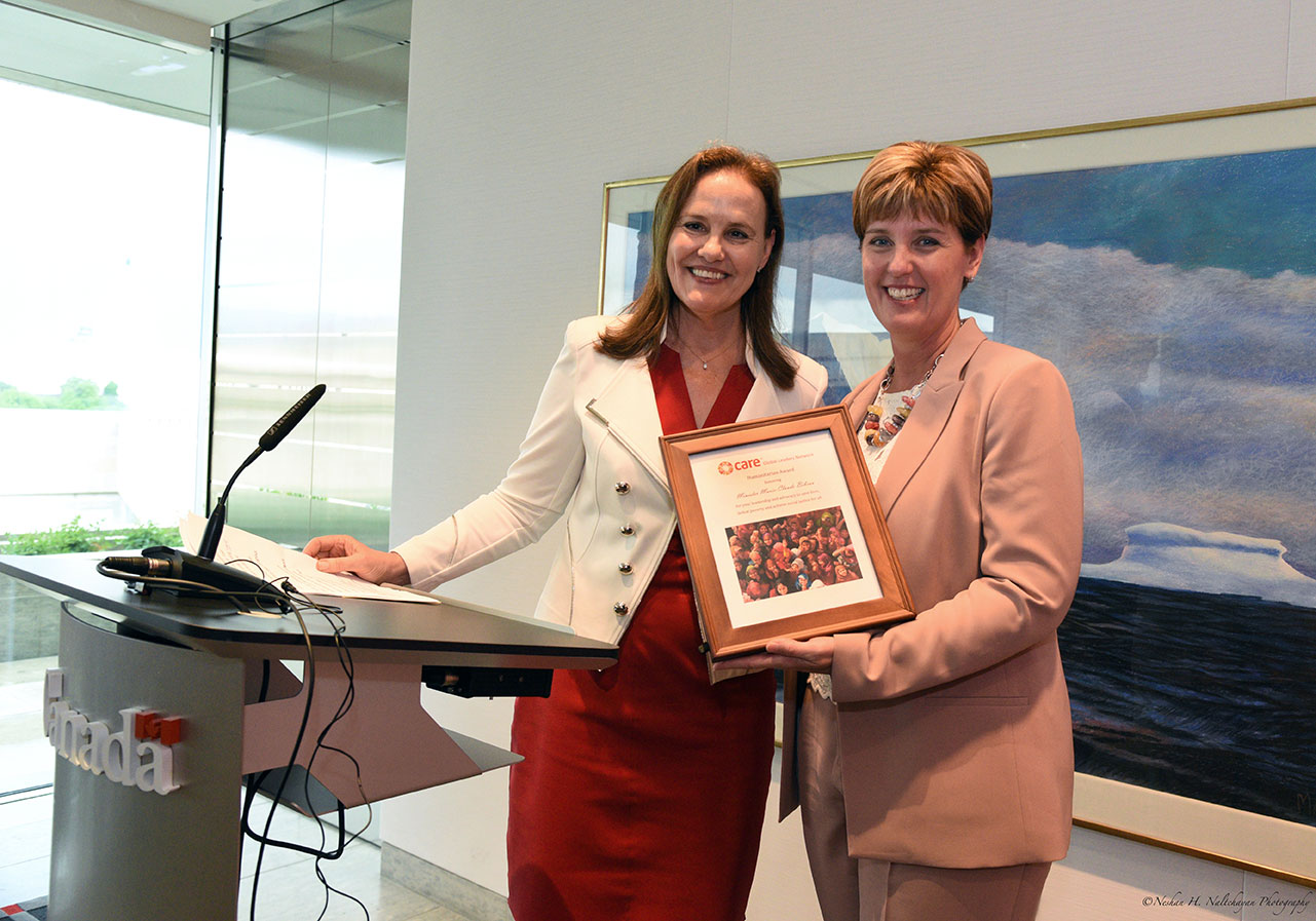 Former Under Secretary of Defense Michéle Flournoy, wearing a red dress and white jacket, stands with Minister Marie-Claude Bibeau, wearing a blush pink suit, as Minister Bibeau accepts a CARE Global Leaders Network Humanitarian Award.