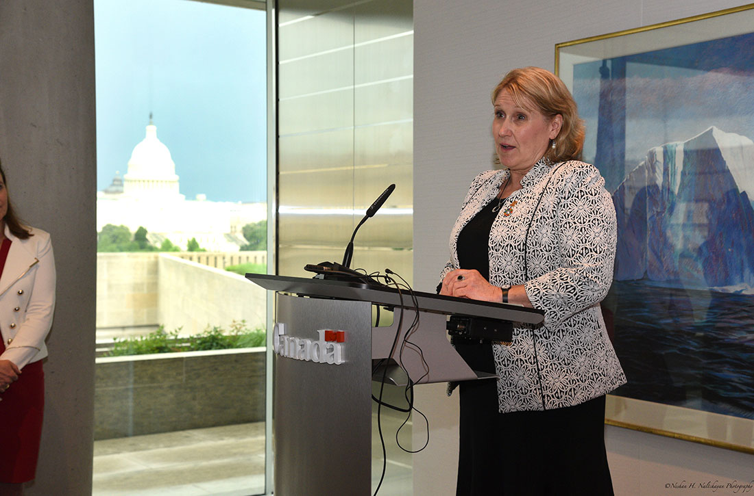 A woman wearing a black and white patterned jacket speaks at the podium at the Embassy of Canada.