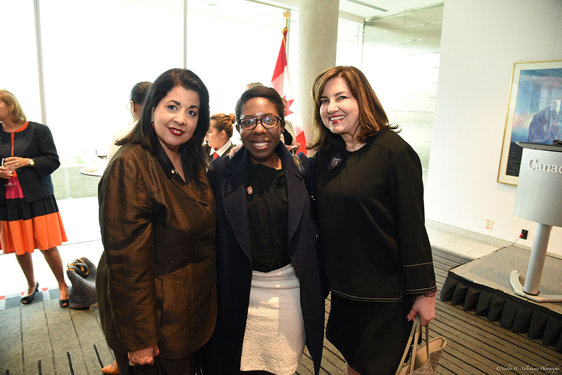 Three female attendees of the event stand together in front of the Canadian flag.