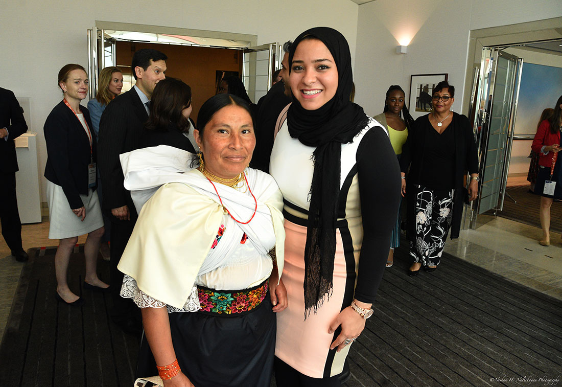 A young woman wearing a black head scarf stands next to a woman wearing a white top and a black shirt with floral embroidery.