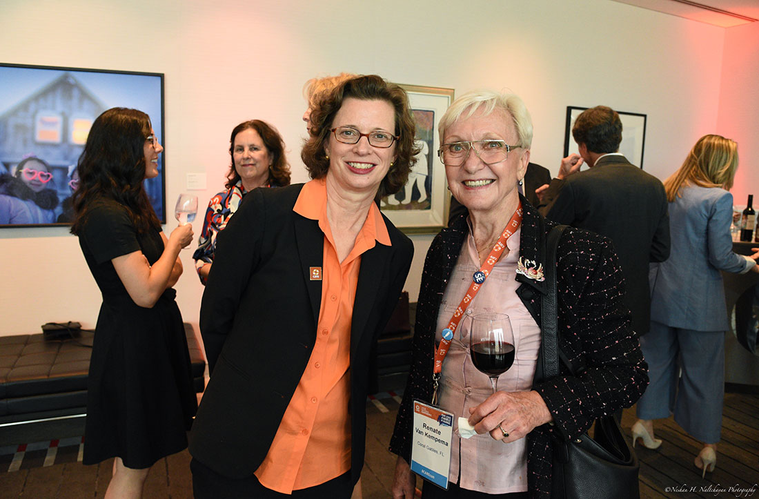 CARE CEO Michelle Nunn stands for a photo next to an attendee of the event, who is wearing an orange CARE lanyard and holding a glass of red wine.