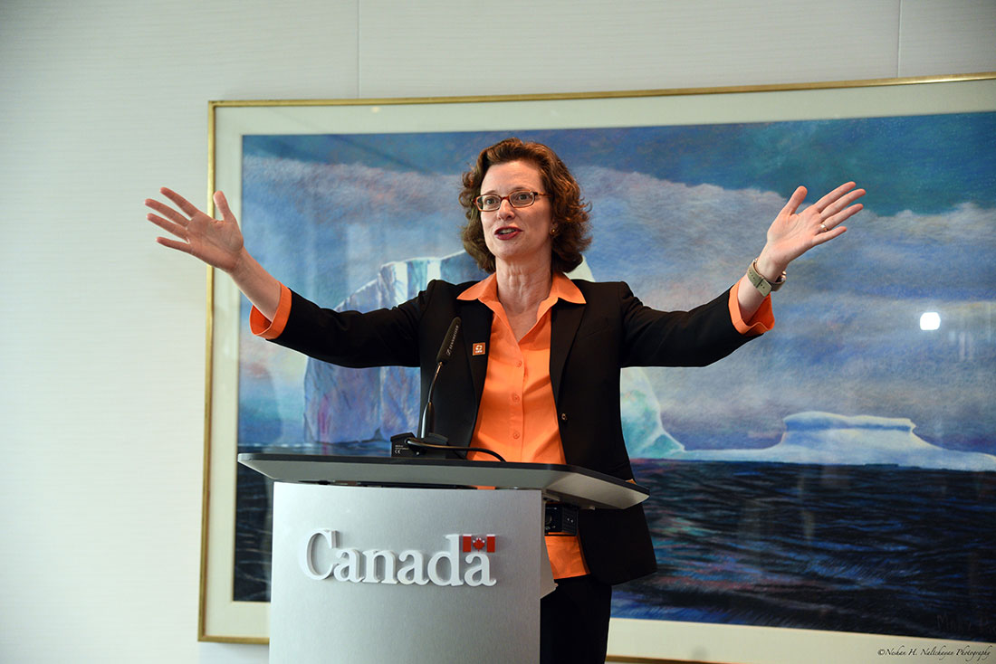CARE CEO Michelle Nunn, wearing an orange blouse, black suit jacket, and orange CARE pin, speaks at the Embassy of Canada podium with her arms outstretched.