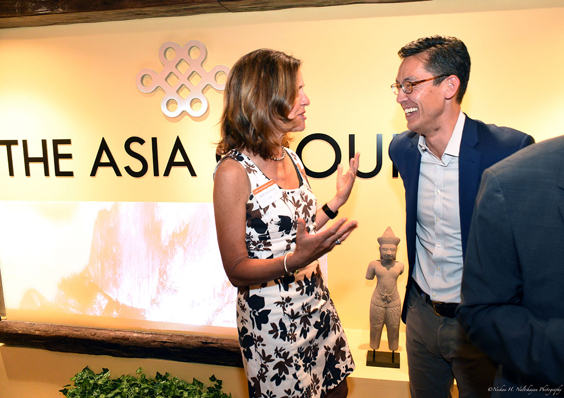 Beth Solomon from CARE speaks with Rexon Ryu, partner of The Asia Group. Behind them is a large sign with The Asia Group logo.