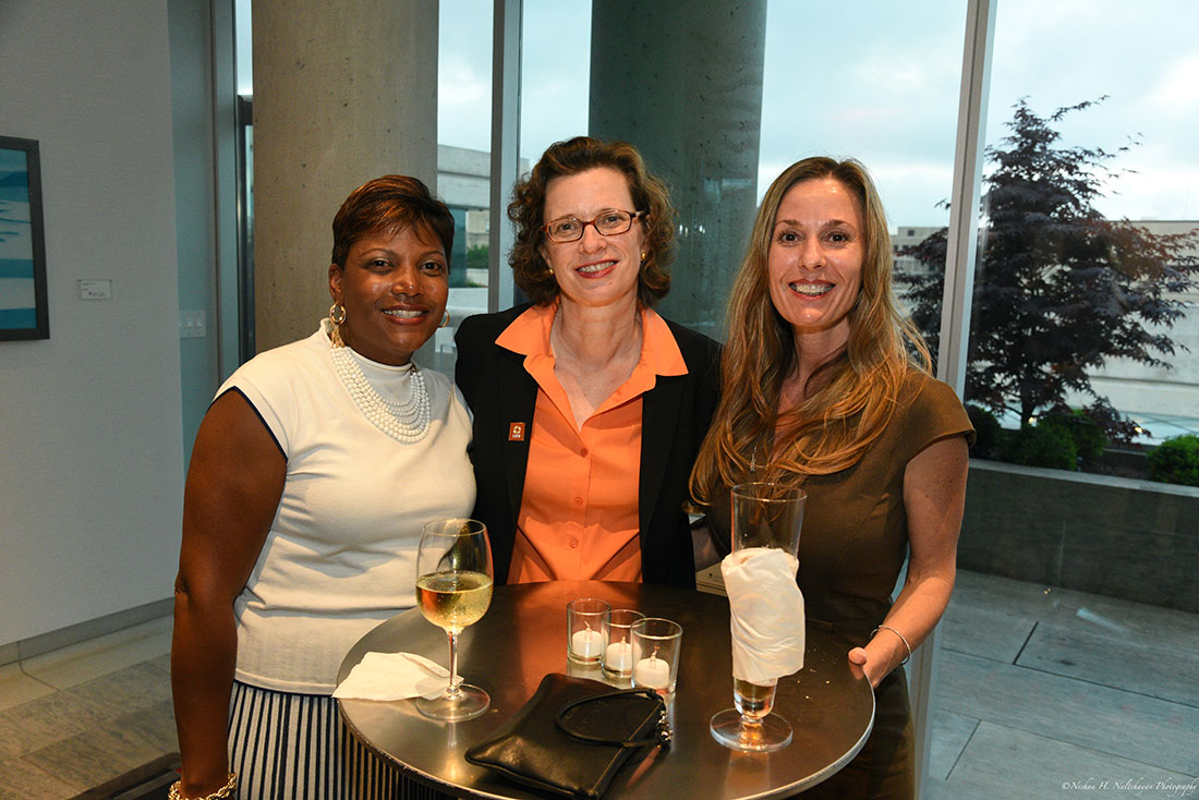 CARE CEO Michelle Nunn, wearing an orange CARE pin and an orange blouse, poses with two attendees at the event.
