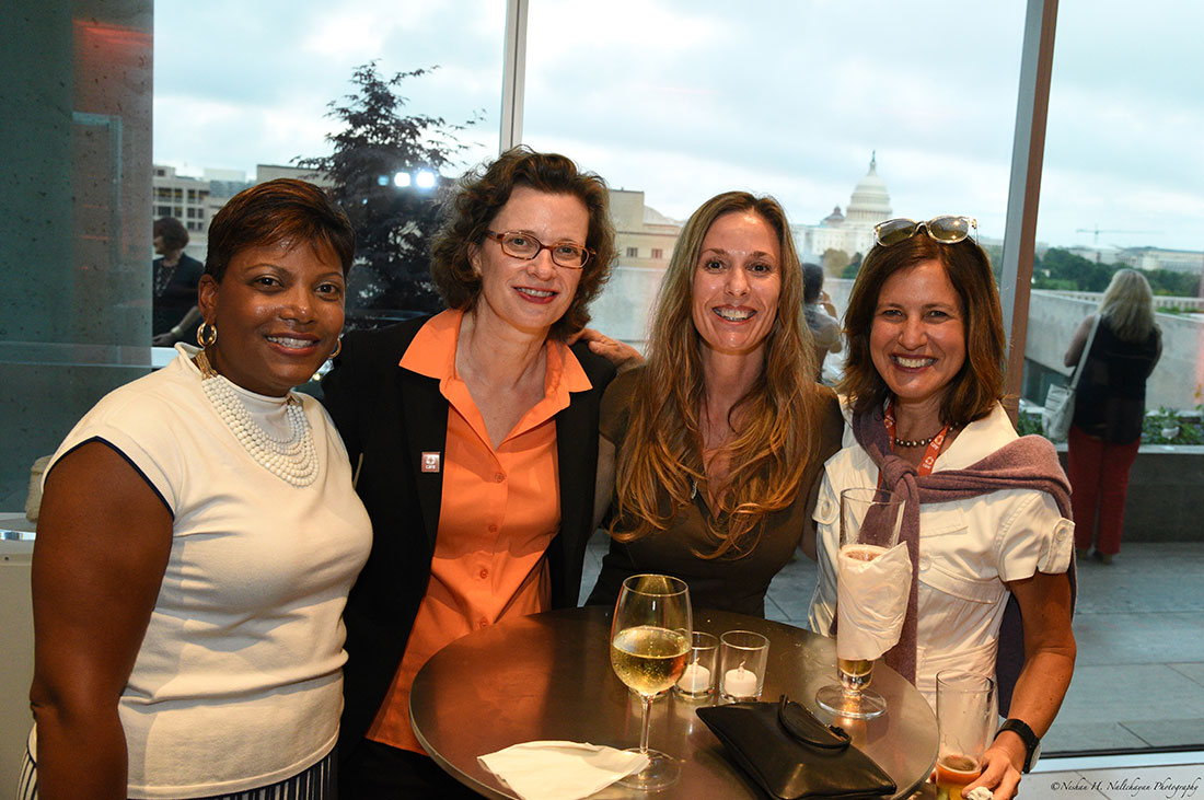 CARE CEO Michelle Nunn, wearing an orange CARE pin and an orange blouse, poses with three attendees at the event.