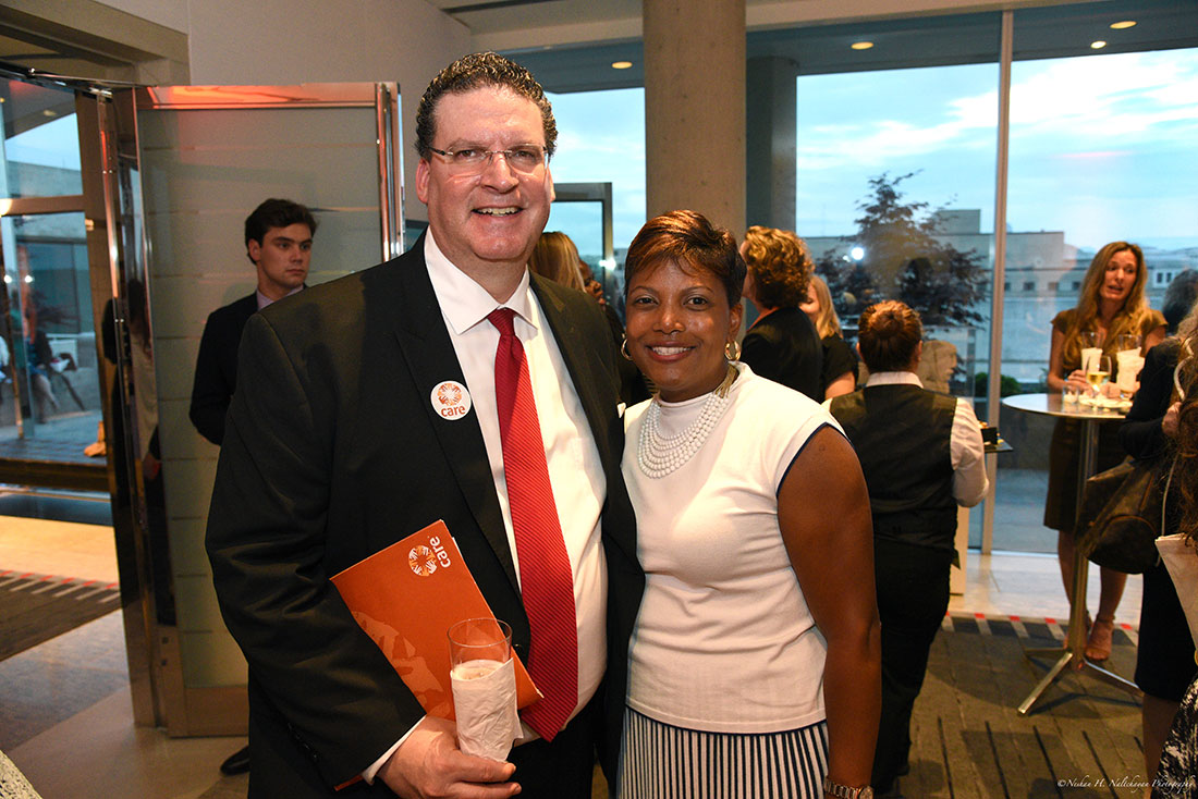A man wearing a CARE pin and holding a CARE folder poses next to a woman.