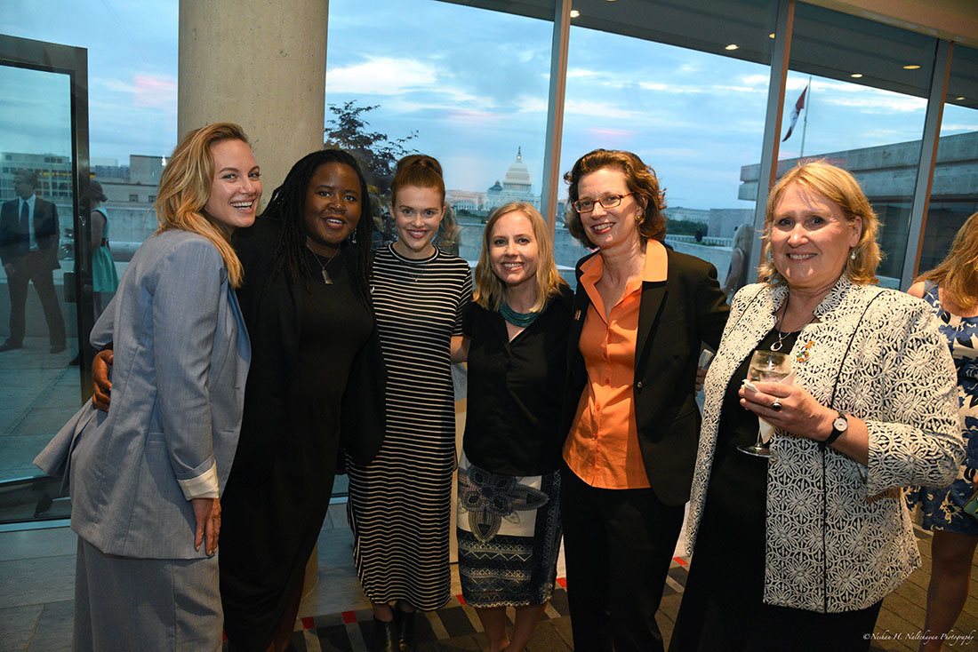 Actresses Danielle Savre and Holland Roden and CARE CEO Michelle Nunn pose for a group photo. The US Capitol building is visible through the window behind them.