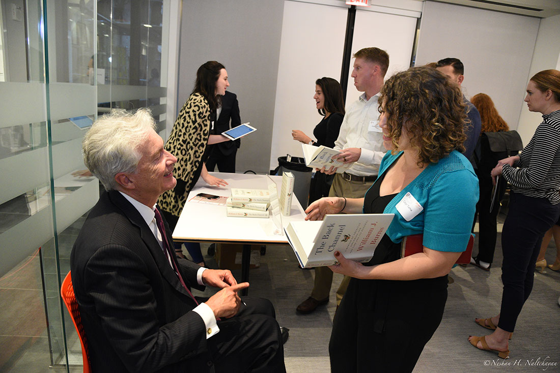 Ambassador William Burns speaks with a woman before signing a copy of his book, The Back Channel.