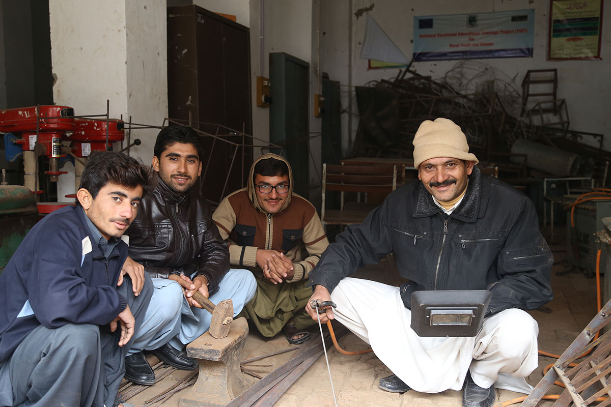 A group of Pakistani men sit on the floor together.