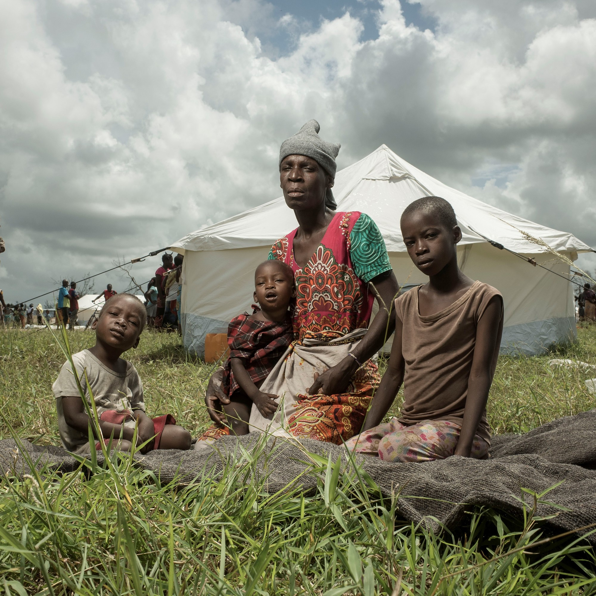 A mother and three of her children sit infant of a temporary shelter.